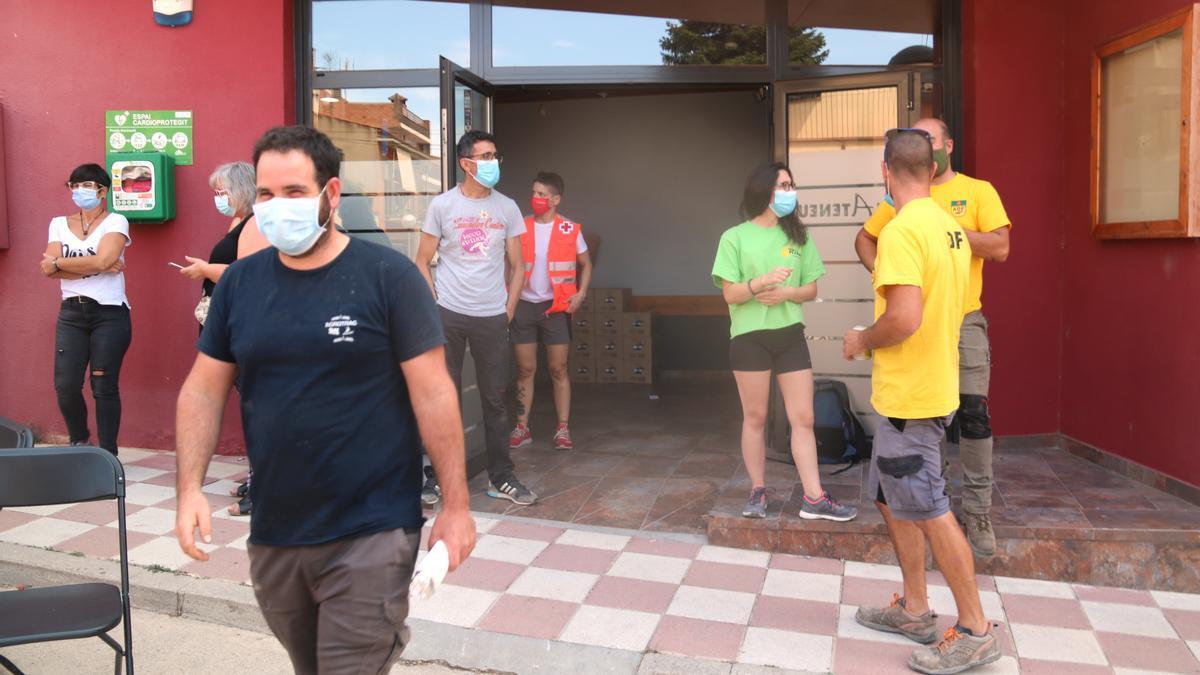 Els voluntaris a l'entrada de l'Ateneu de Sant Martí de Tous que participen en les tasques per apagar el foc que crema a les comarques de la Conca de Barberà i l'Anoia.