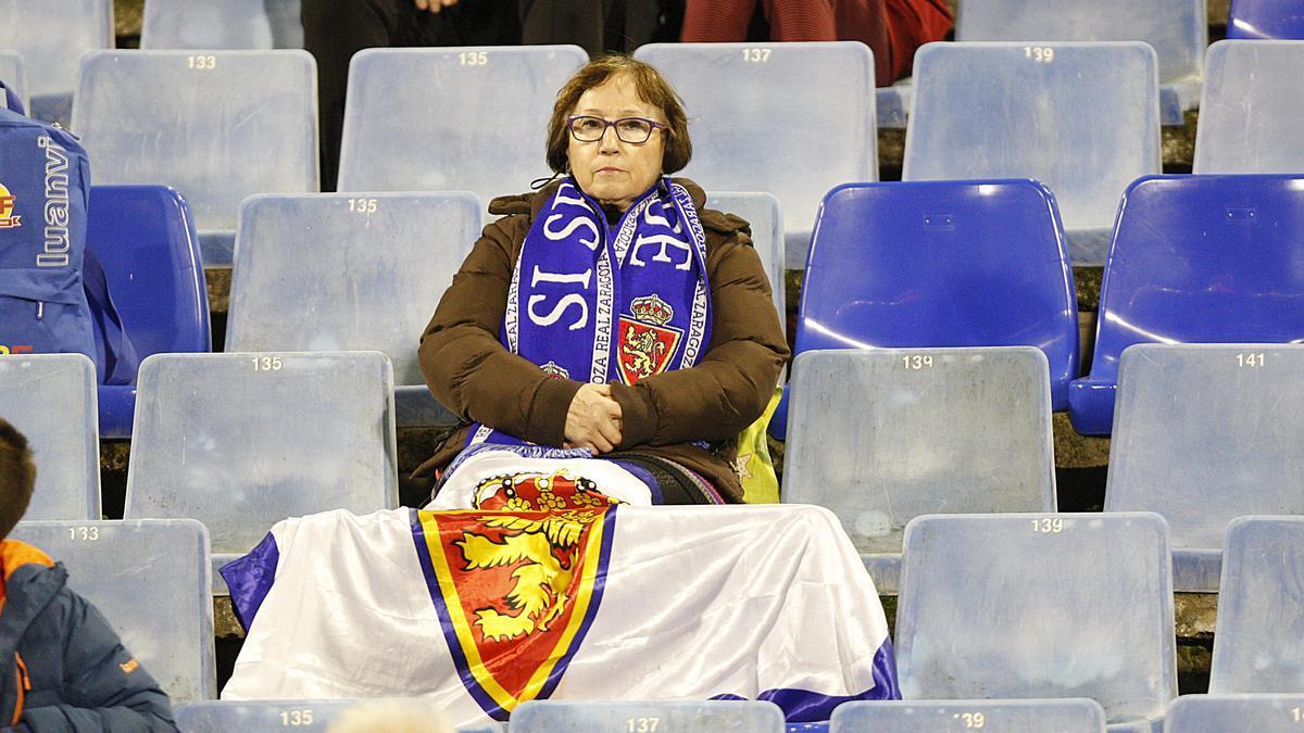 Una aficionada, con semblante serio en su asiento de La Romareda.