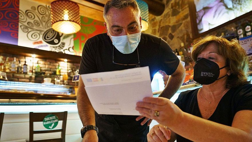 Una mujer muestra su certificado covid en el interior de una cafetería.