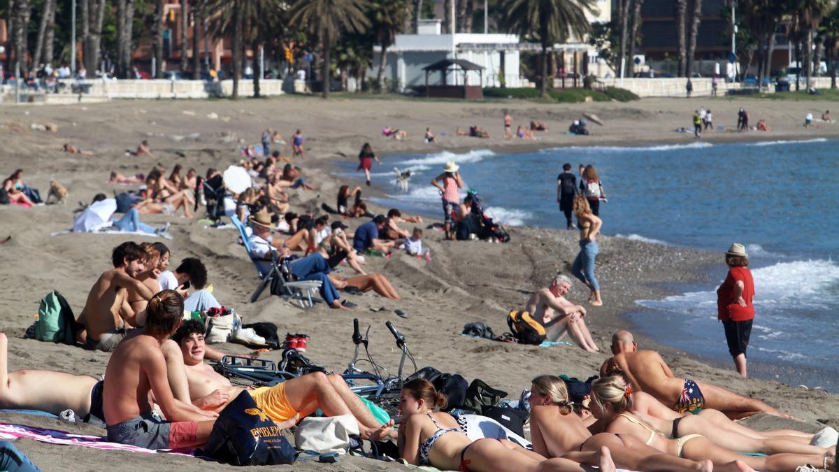 Personas tomando el sol en la playa