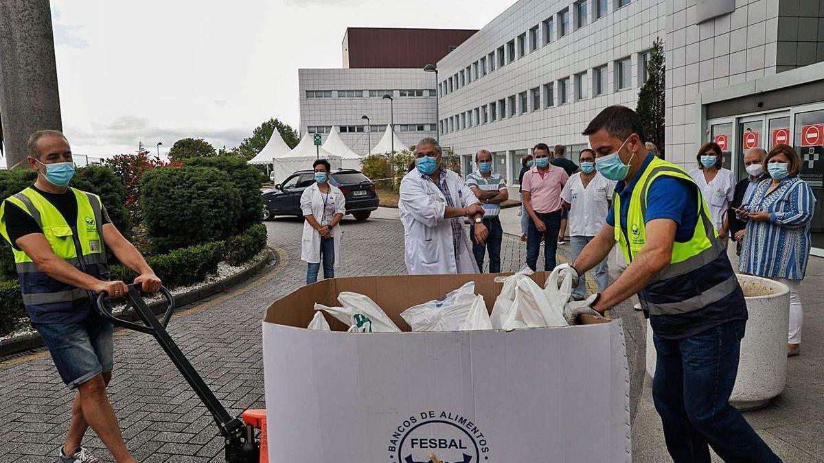 Voluntarios del Banco de Alimentos recogen los productos ante la mirada de responsables del área sanitaria, ayer a mediodía en el Hospital Universitario San Agustín.