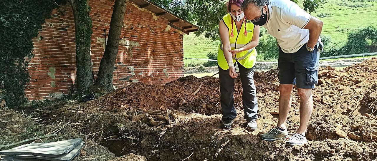 Arantza Margolles, arqueóloga de la asociación, mostrando en julio de 2020 los restos hallados en la fosa de El Rellán a Ramón Miranda, vecino de Grado, que cree que tiene allí a un tío materno enterrado. | S. Arias