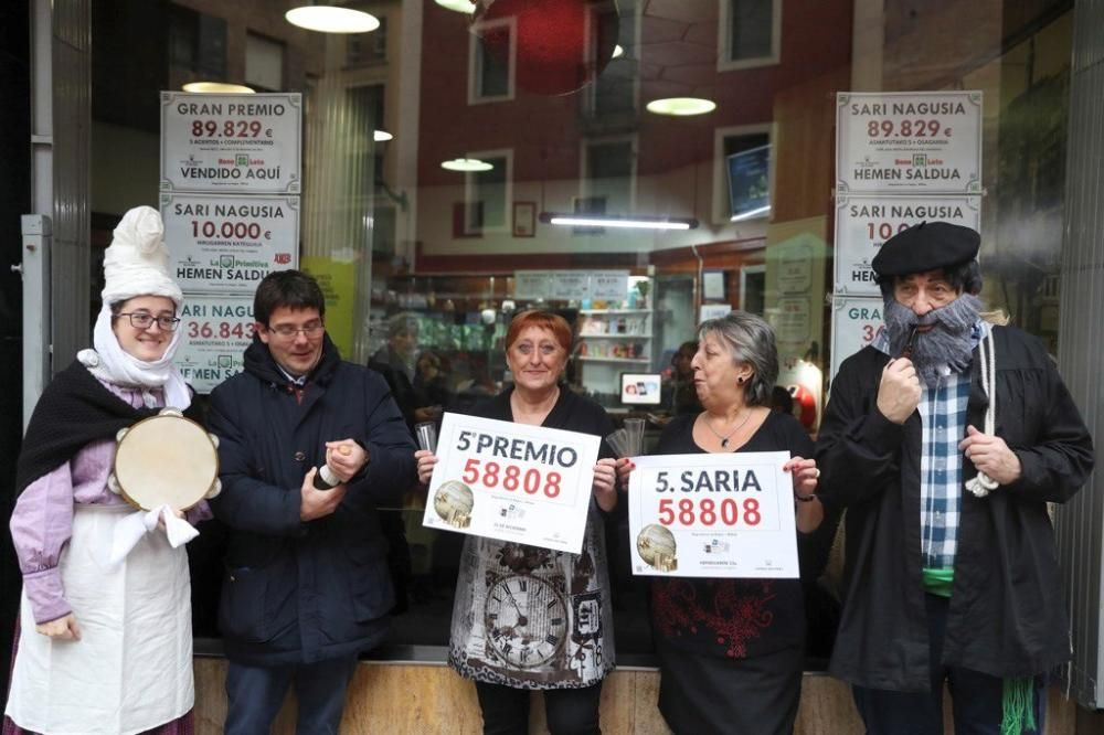 Las loteras María Jesús (d) y Begoña junto al Olentzero (d) celebran el reparto del número 58808, quinto premio de la lotería de Navidad, que le ha tocado al número 58808, en un punto de venta de la calle Castaños de la capital vizcaína. EFE