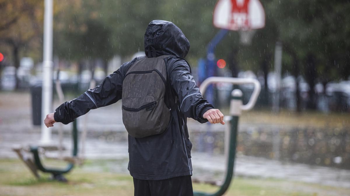 Una persona con un chubasquero bajo la lluvia en una imagen de archivo.