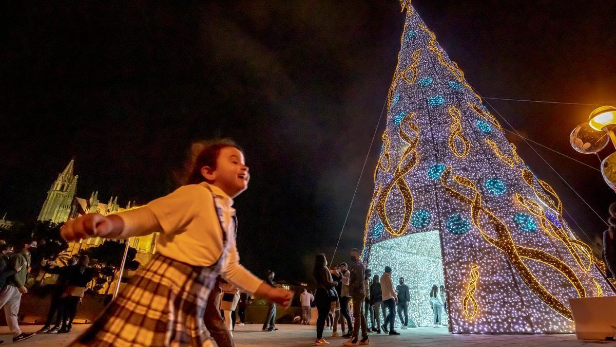 Una niña juega delante del árbol de Navidad instalado en el Parc de la Mar, en Palma.
