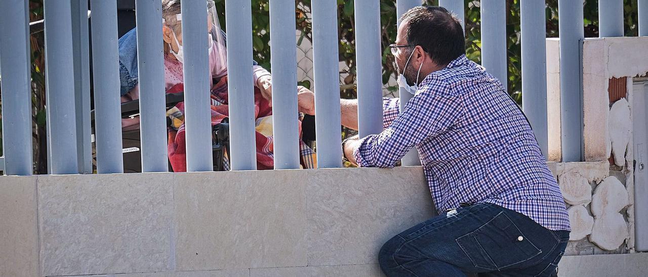 Una familiar saluda a una persona mayor en su residencia, a través de la valla, durante la pandemia. |