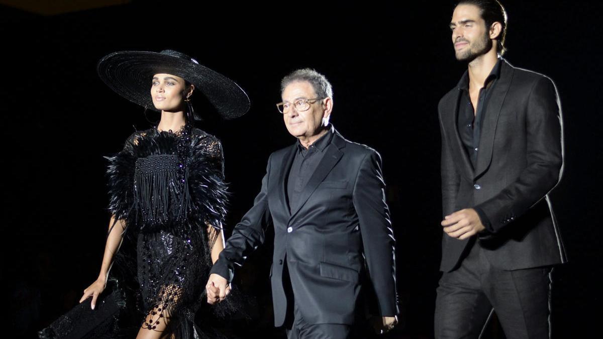 Dos modelos desfilan junto con el diseñador Roberto Verino.