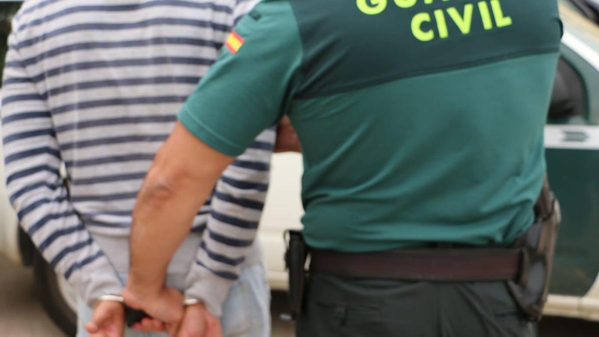 Un guardia civil traslada a uno de los detenidos