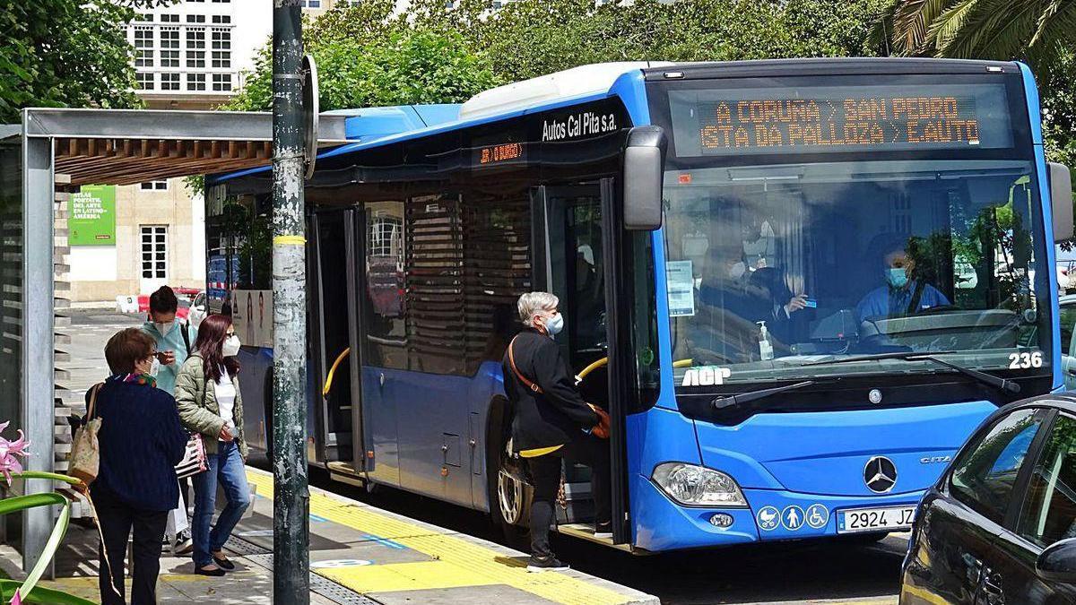 Pasajeros del autobús interurbano en la parada de Entrejardines de A Coruña.