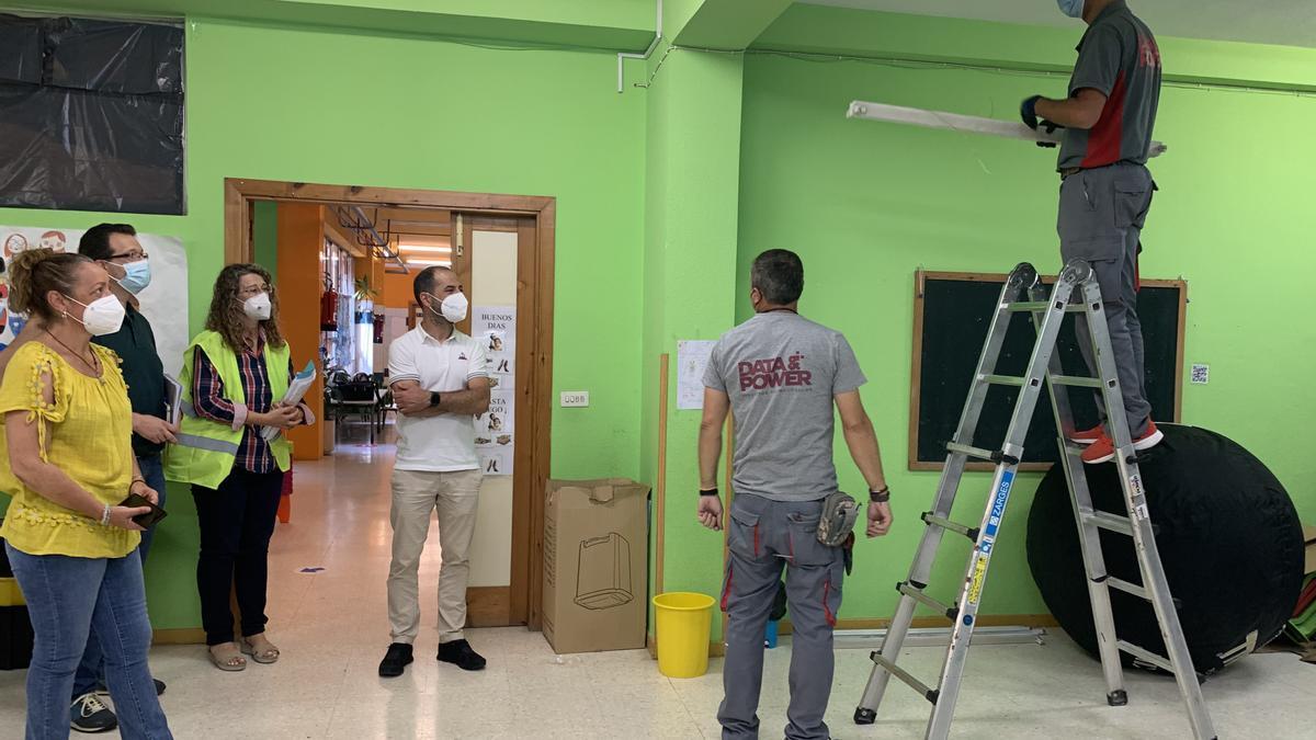 El alcalde, junto a la puerta, con operarios y responsables del centro, en el colegio, donde se ha iniciado la renovación de la instalación eléctrica.