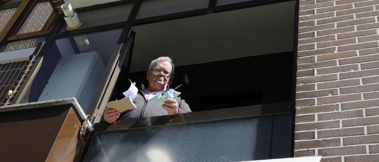 Javier Lamela, en la ventana de su casa de Gijón, durante el confinamiento.