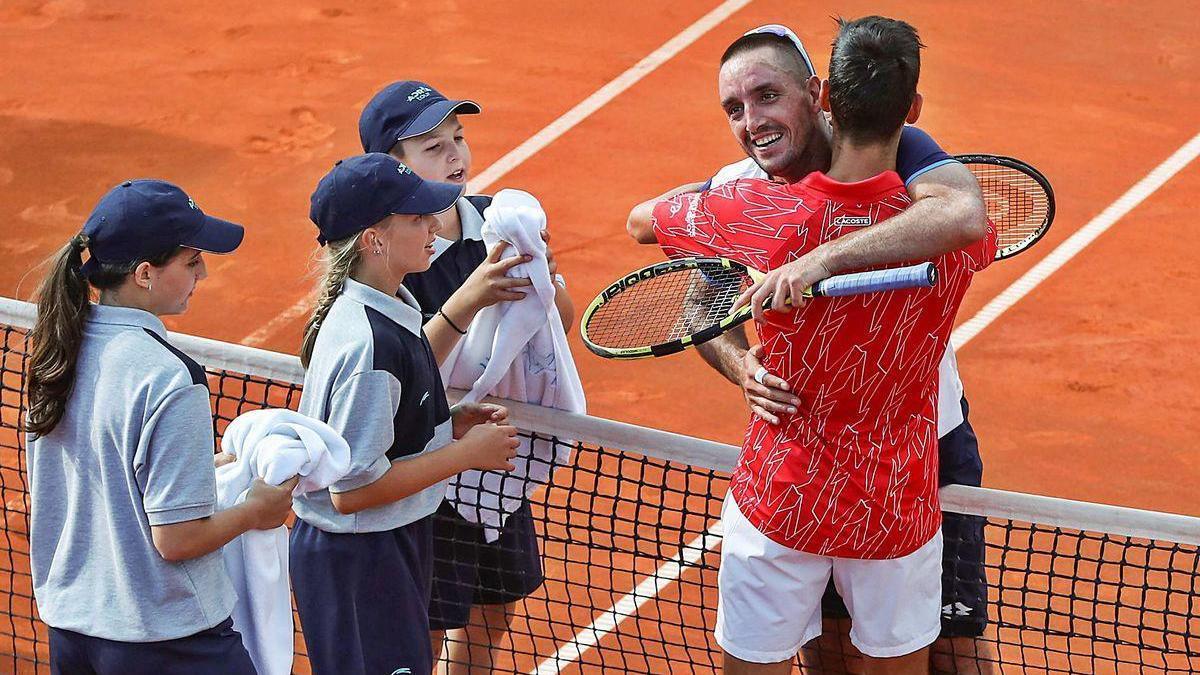 Djokovic (de espaldas) y Troicki se abrazan ante varios recogepelotas durante el Adria Tour.
