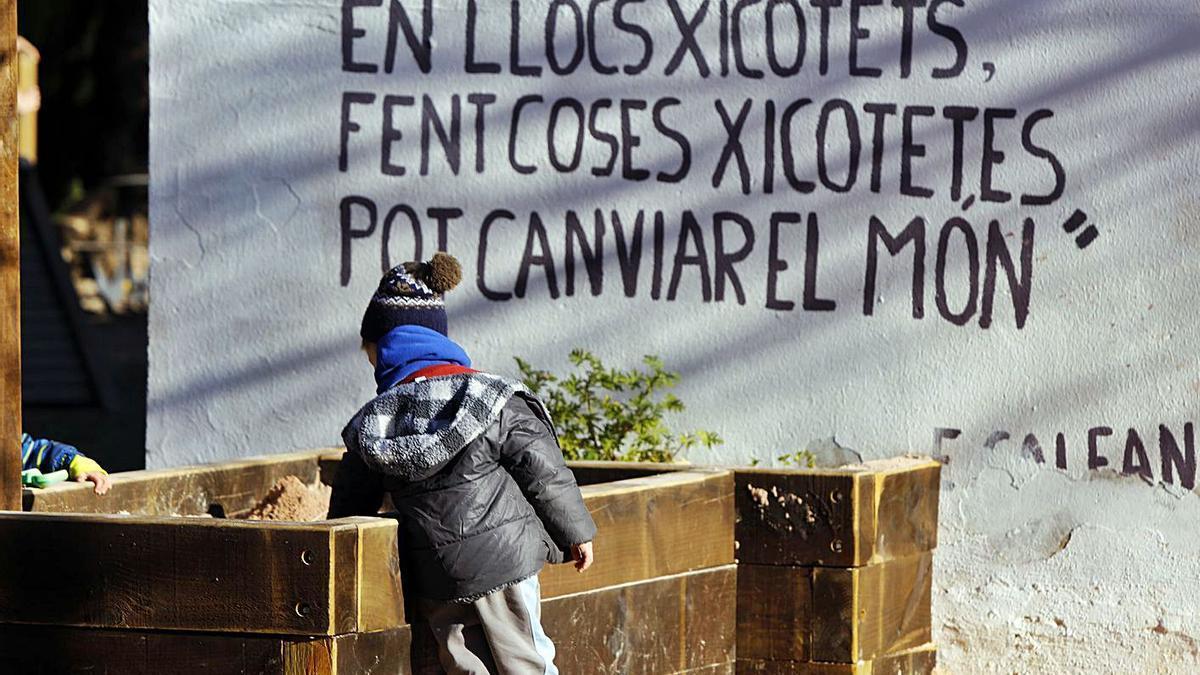 Un escolar juga amb la terra davant d'una cita de l'escriptor Eduardo Galeano. | M.Á.MONTESINOS