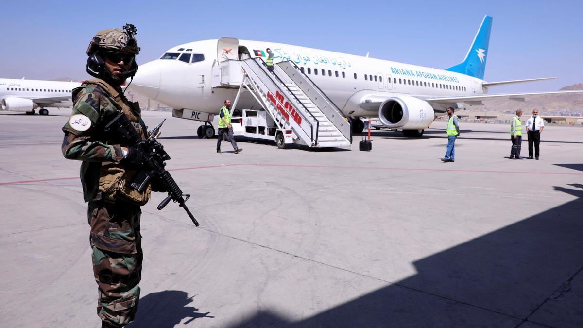 Un miliciano junto a un avión en el aeropuerto de Kabul.