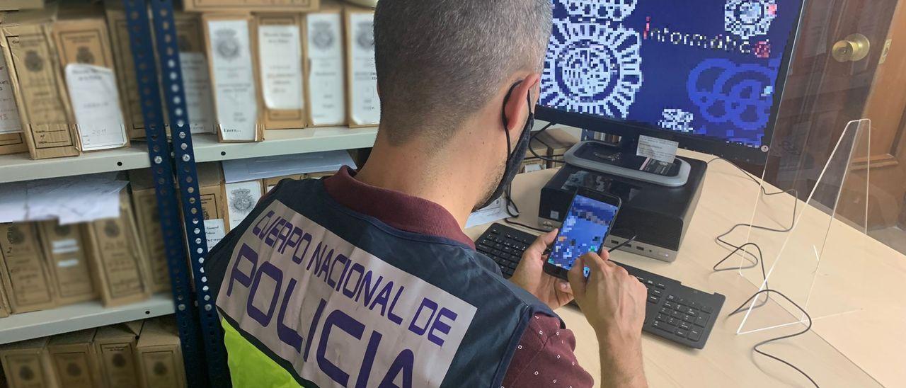 Un miembro del grupo que ha llevado la investigación examina un dispositivo móvil.