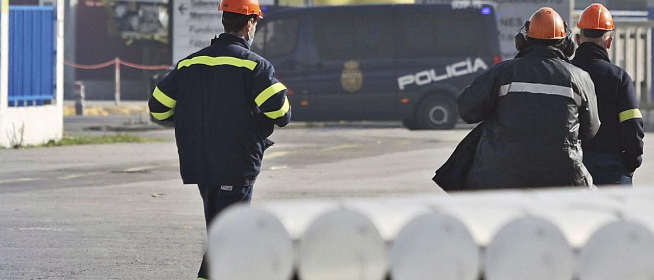 Trabajadores de Alu  Ibérica, en las instalaciones de San Balandrán, frente a un vehículo policial durante el registro del jueves. | Ricardo Solís