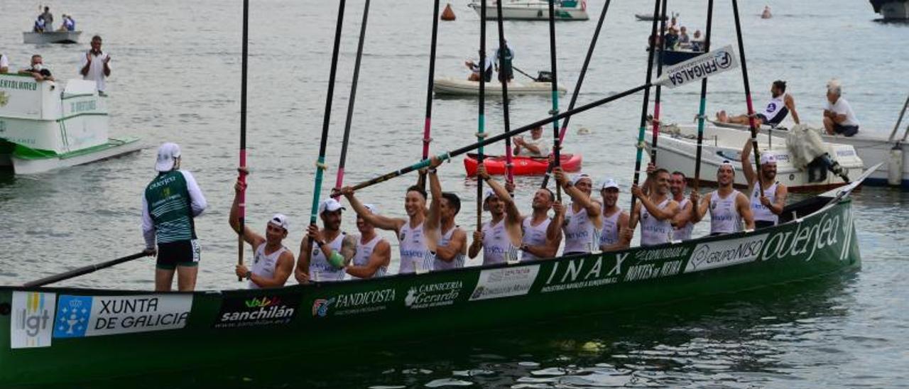 La tripulación de Meira alza sus remos para festejar la victoria. | GONZALO NÚÑEZ