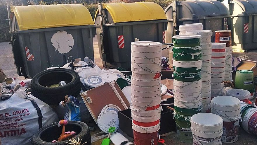 Tiran en Xàbia fuera de los contenedores cubos de pintura y neumáticos
