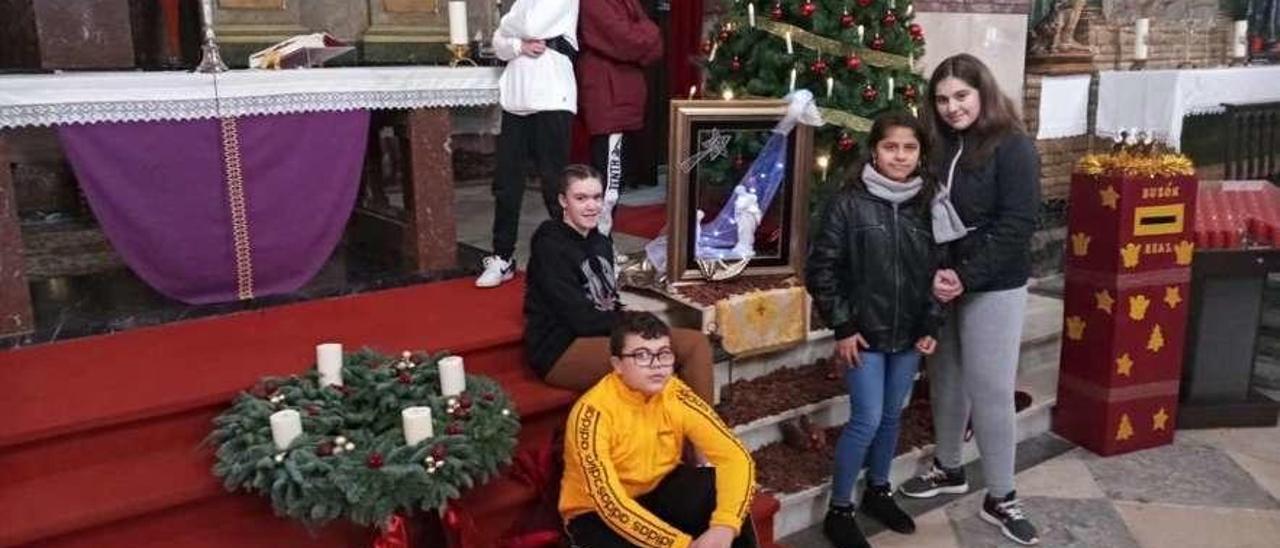 Iván Núñez y Javier Amago, detrás, de pie; sentados, Aroa Menéndez y Gabriel Remoir, y de pie, a la derecha, Asly Oliva y Lucía Rodríguez, en el altar de la iglesia veigueña, junto a la decoración navideña.