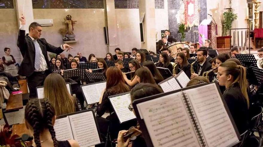 De pie, el director de la banda dirige una de las piezas del concierto en la iglesia del Carmen.