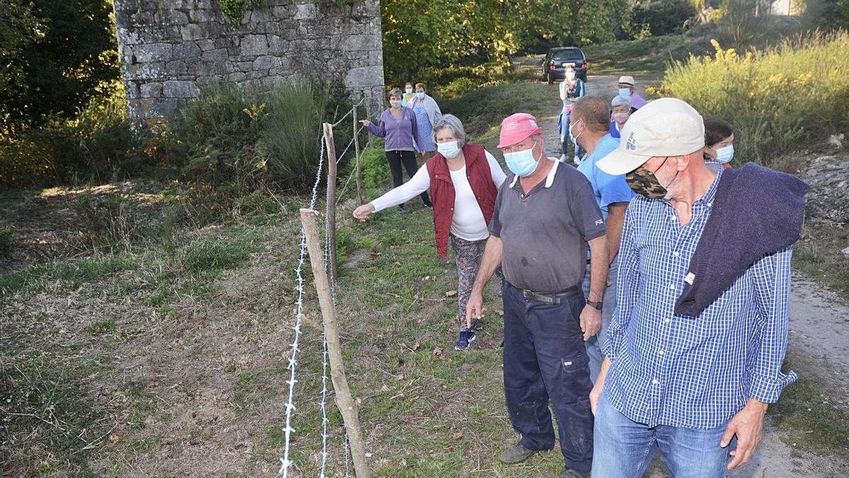 Vecinos muestran el alambre de espino por el que protestan y que ordena retirar el Concello.     // R.VÁZQUEZ