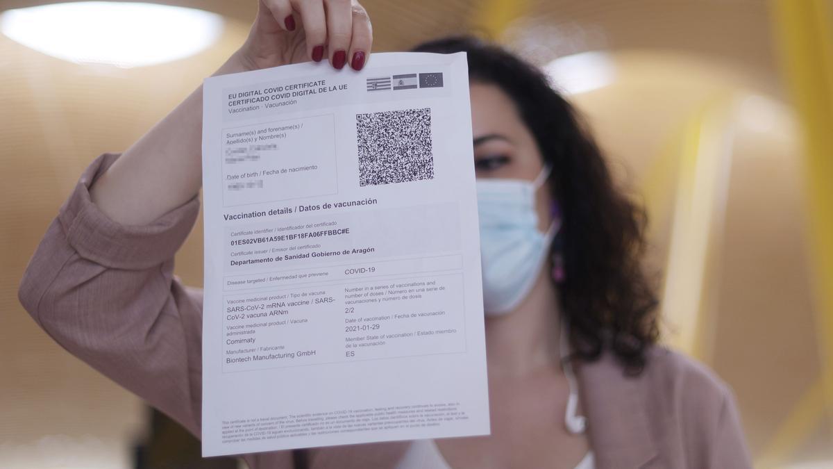 Una mujer muestra su certificado de vacunación en Barajas.