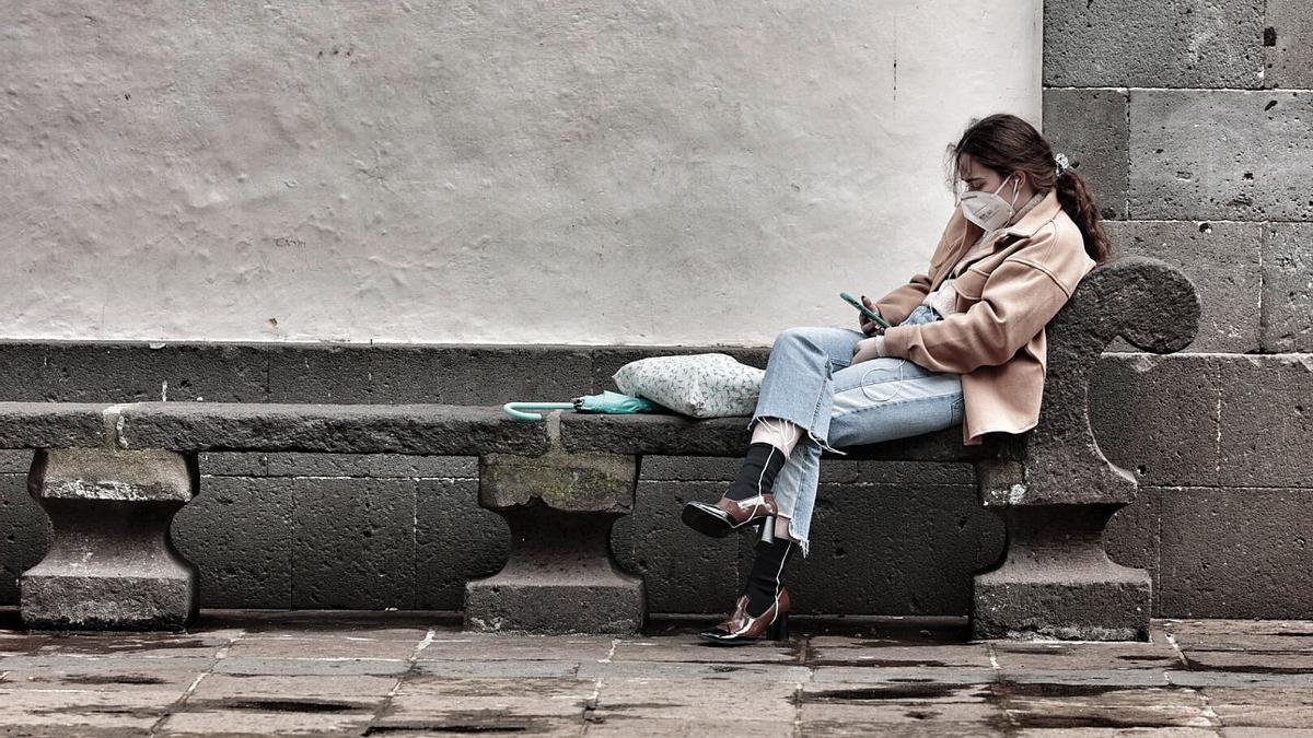 Una joven mira el móvil en los aledaños de la Catedral de San Cristóbal de La Laguna.