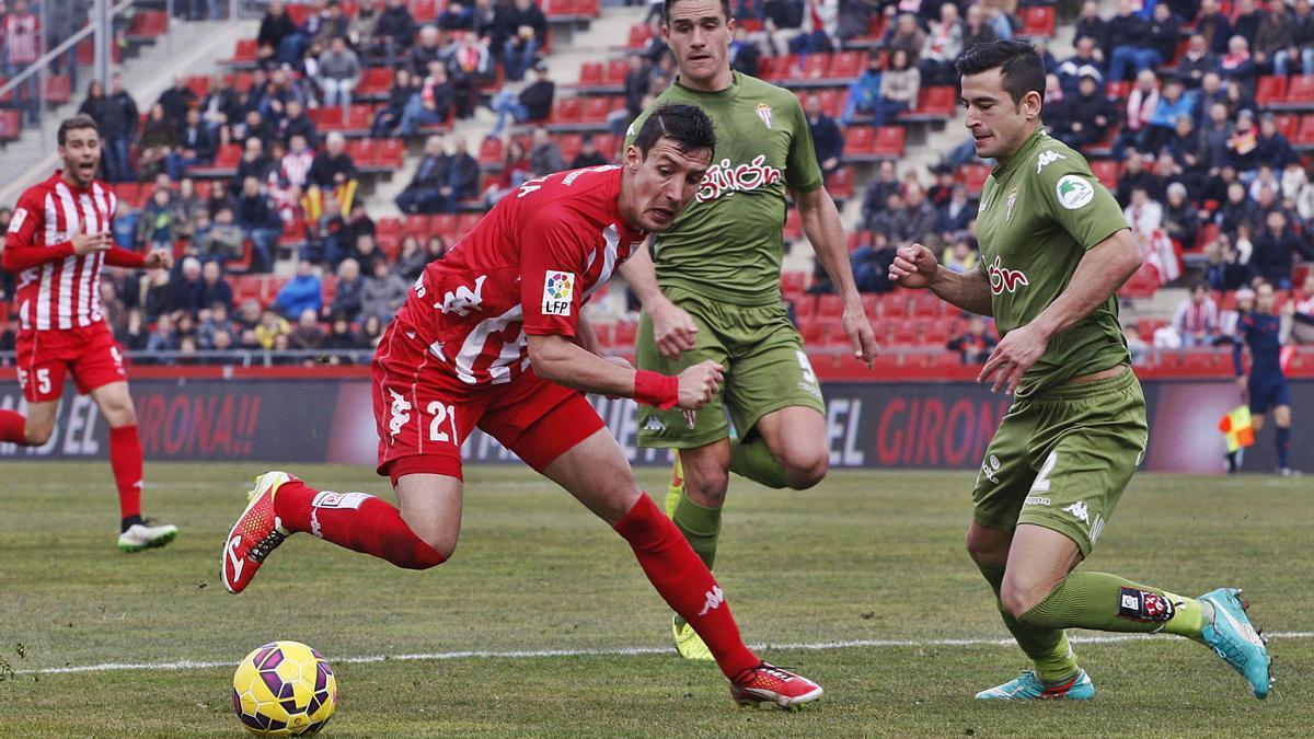 Sandaza intenta desempellegar-se de Luis Hernández i de Bernardo Espinosa en el 0-0 contra l'Sporting en Lliga a Montilivi.   MARC MARTÍ
