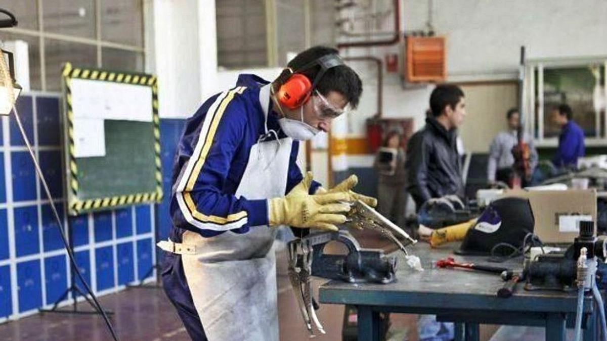 33 Un joven manipula una máquina en un curso de Formación Profesional.   EL PERIÓDICO