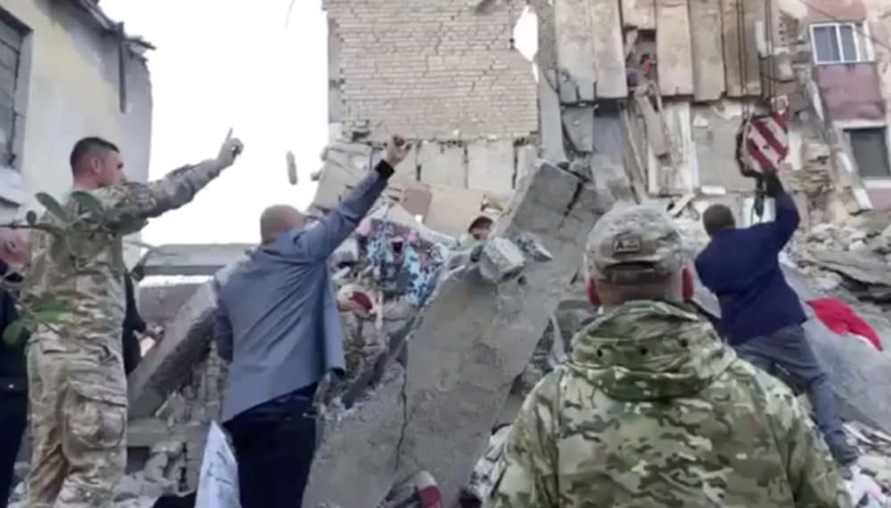 Military personnel and locals remove debris from ...