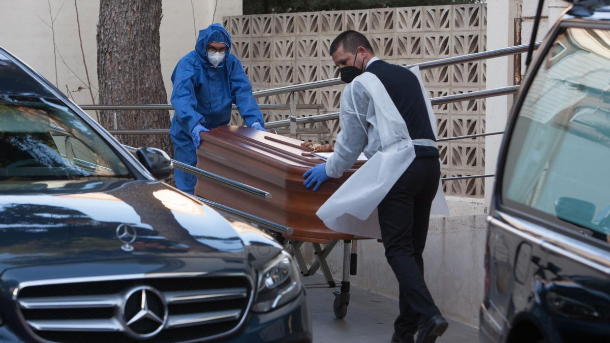 Operarios trasladan el ataúd de un fallecido.