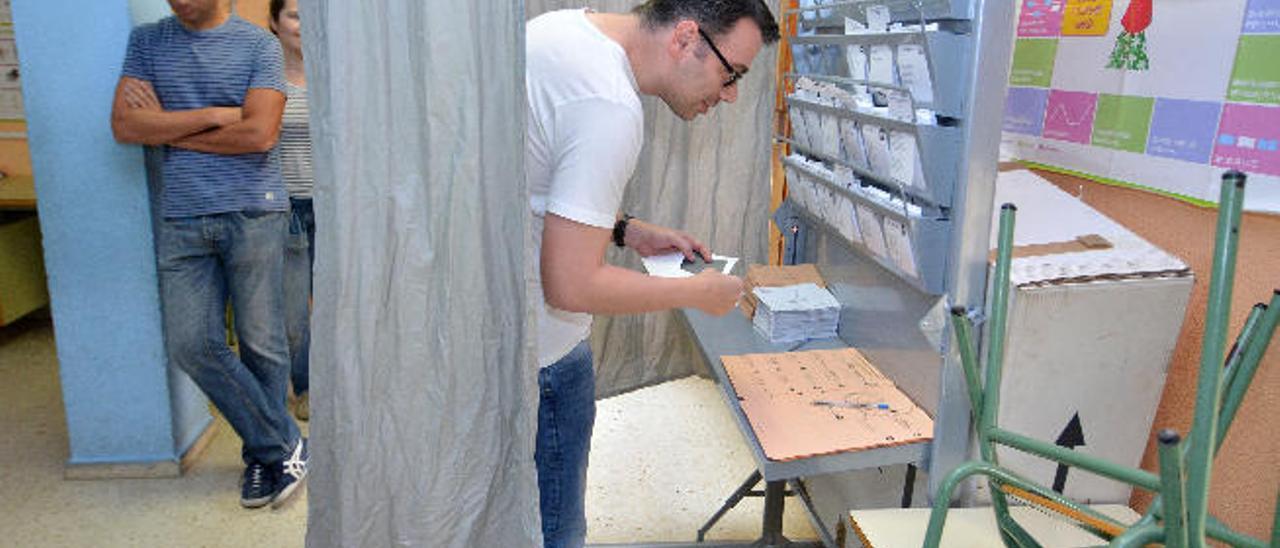 Un elector busca una papeleta para ejercer el voto en las pasada elecciones generales, en un colegio electoral de Telde.