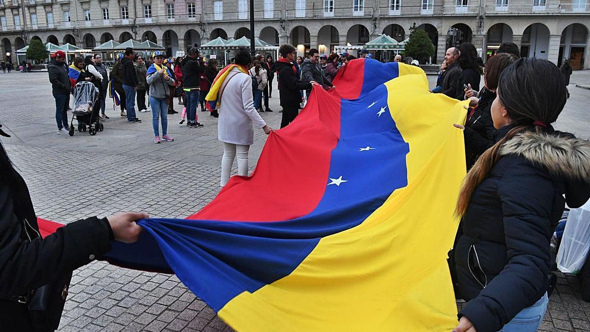 Un grupo de venezolanos extiende la bandera de su país en la plaza de María Pita. |   // VÍCTOR ECHAVE