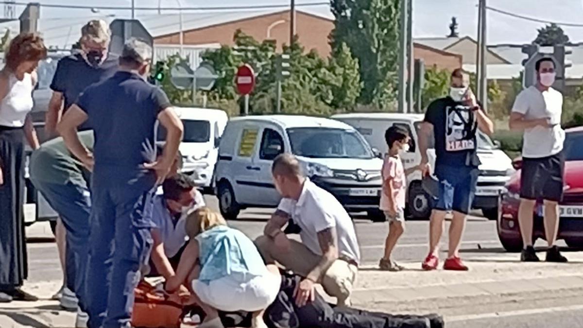 El herido, en el suelo, atendido por varios ciudadanos tras los disparos.