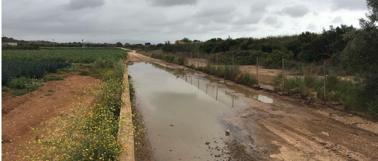 Acumulación de agua en el camino paralelo a la autopista en Benicarló, cortado a la altura del barranco de Soriano