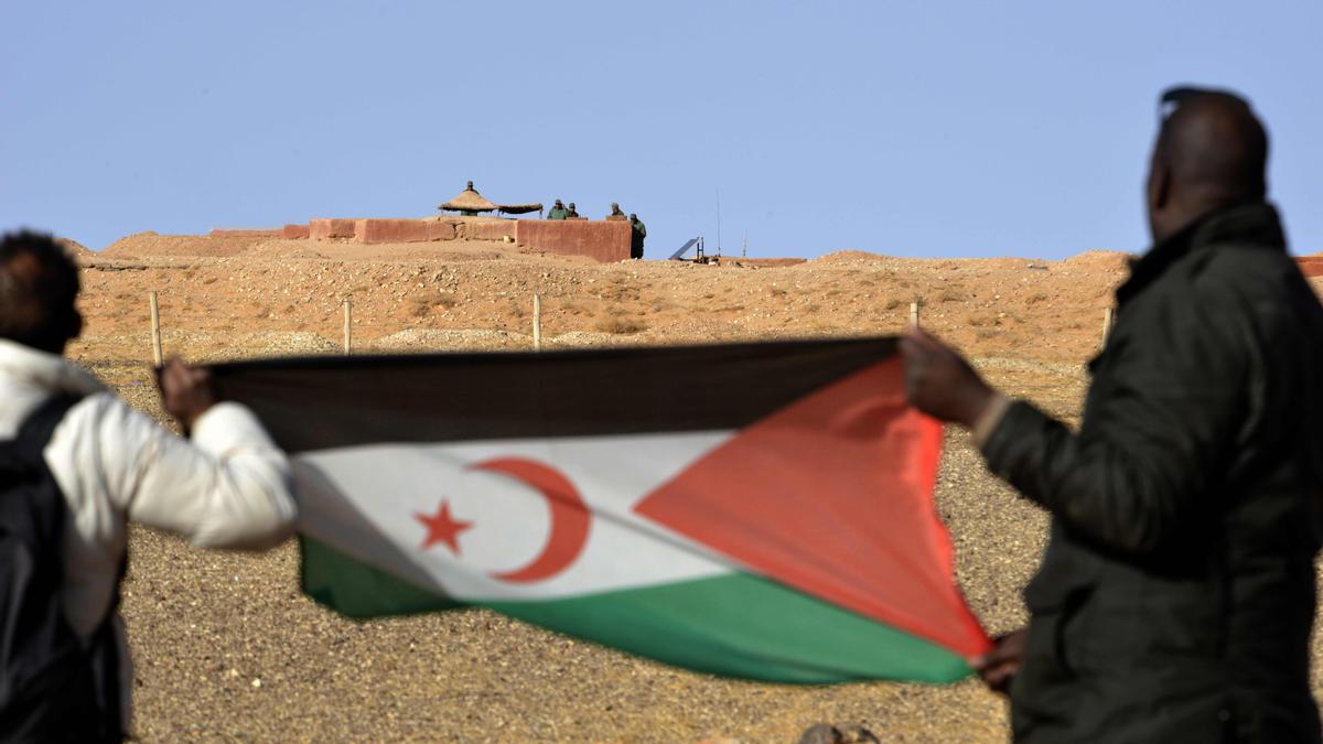 Dos hombres alzan una bandera del Frente Polisario.