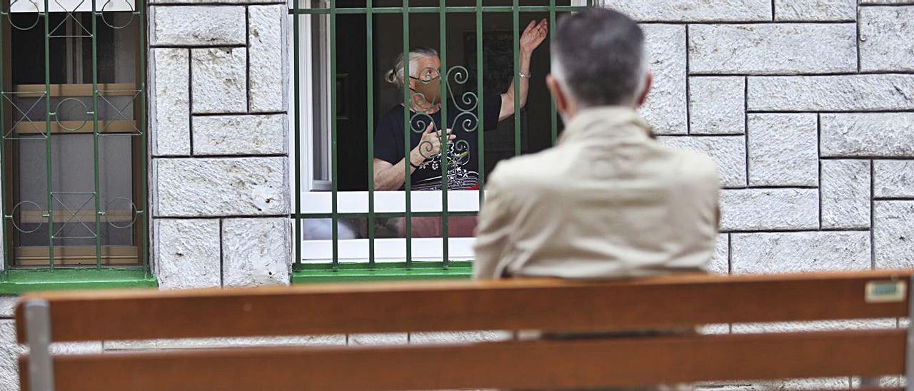 Un hombre sentado en el banco instalado frente a la casa de Edmé González observa a la mujer dentro de su cocina. Ricardo Solís