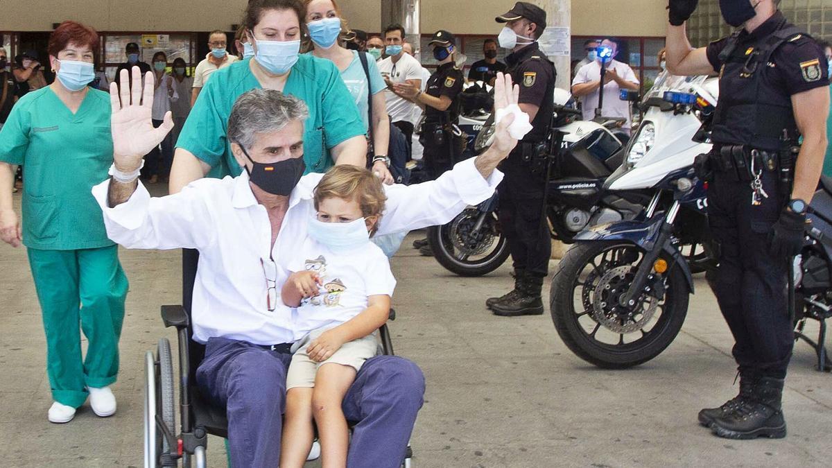 El policía nacional José del Castillo con su nieto el día en que recibió el alta y el homenaje de sus compañeros tras  75 días ingresado por covid, 50 de ellos en la UCI. | PILAR CORTÉS