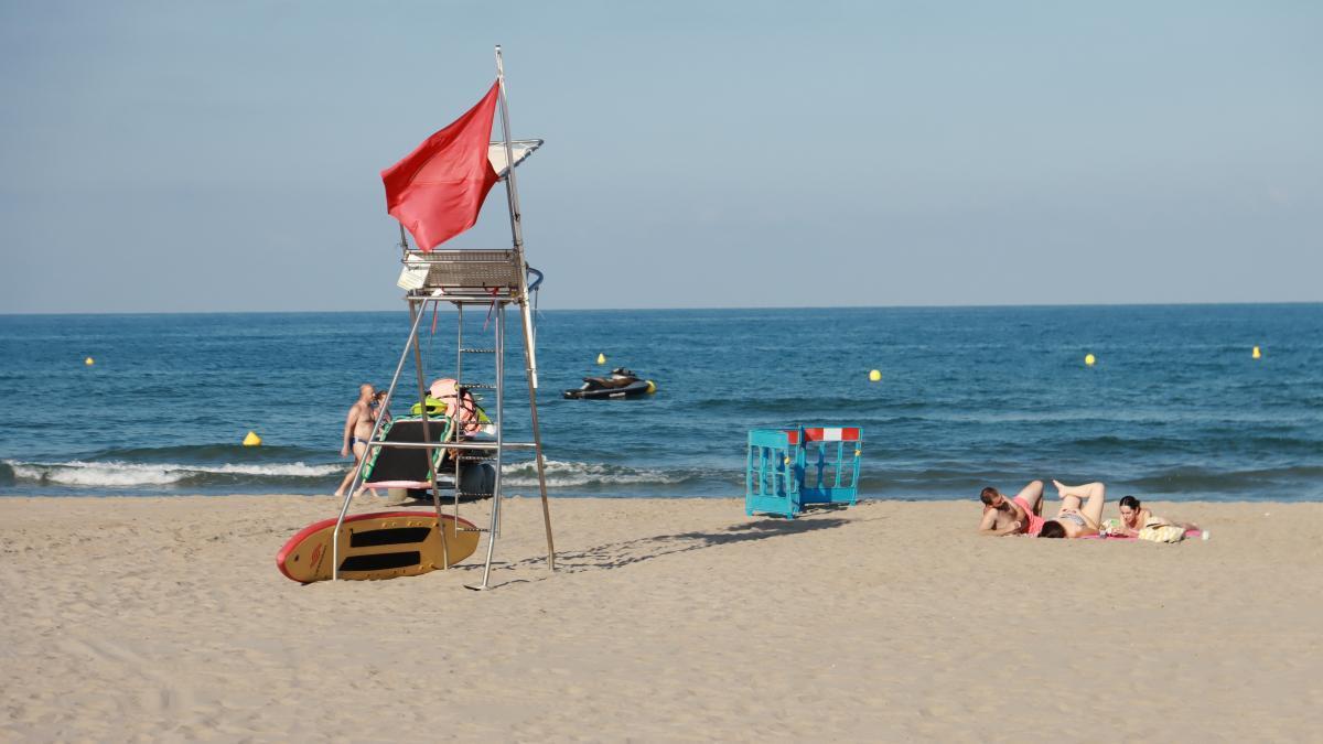 La playa del Gurugú de Castelló, en julio, también con la bandera roja que indica la prohibición del baño en sus aguas.