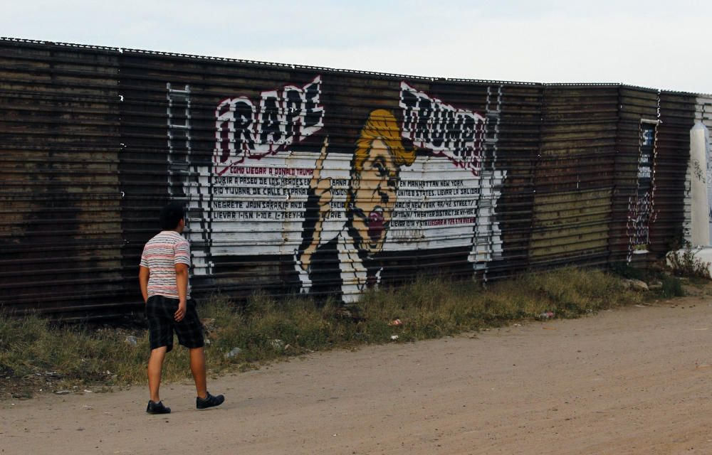 Un ciudadano de la ciudad de Tijuana, México, camina frente a una caricatura de Trump pintada en el muro de la frontera con Estados Unidos.
