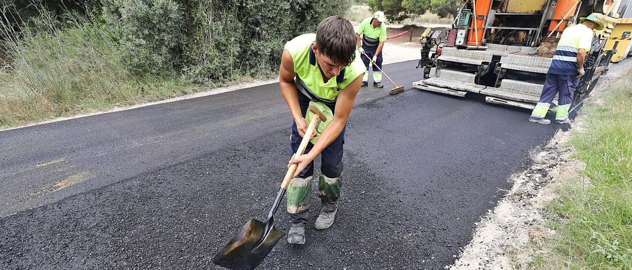 Operarios asfaltando el Camino del Carabasí, que une la playa ilicitana con el término de Santa Pola, este jueves