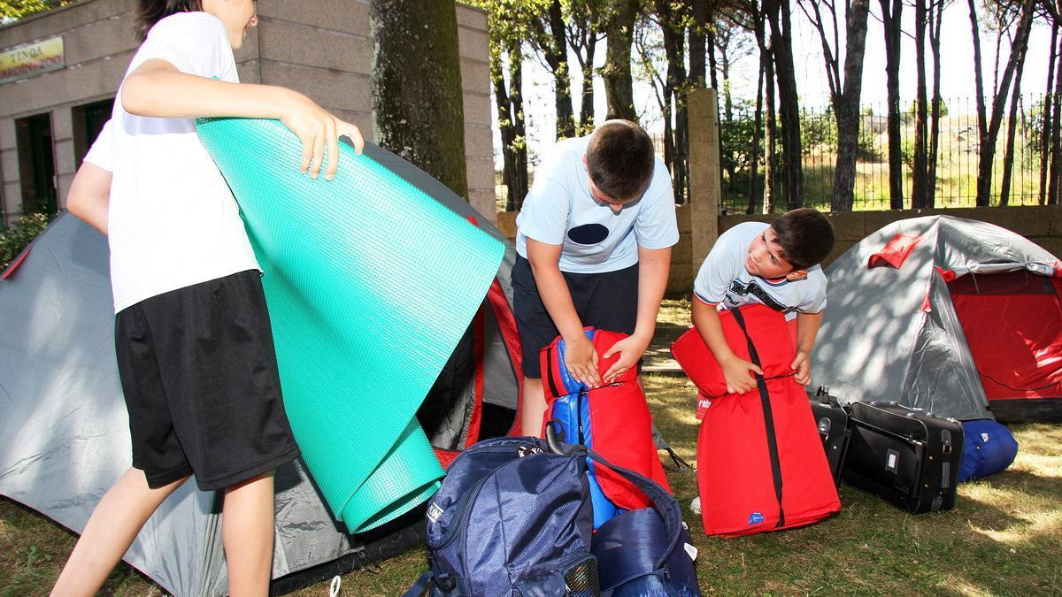 Un grupo de niños preparando las tiendas de campaña.