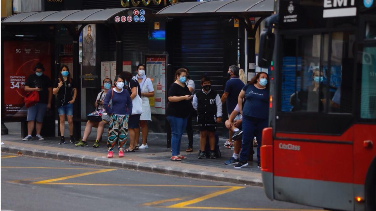 Un grupo de usuarios espera el autobús en la parada de la calle San Vicente Ferrer.