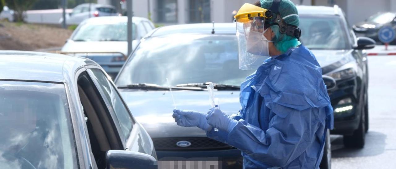 Un enfermero toma muestras a un paciente desde su vehículo