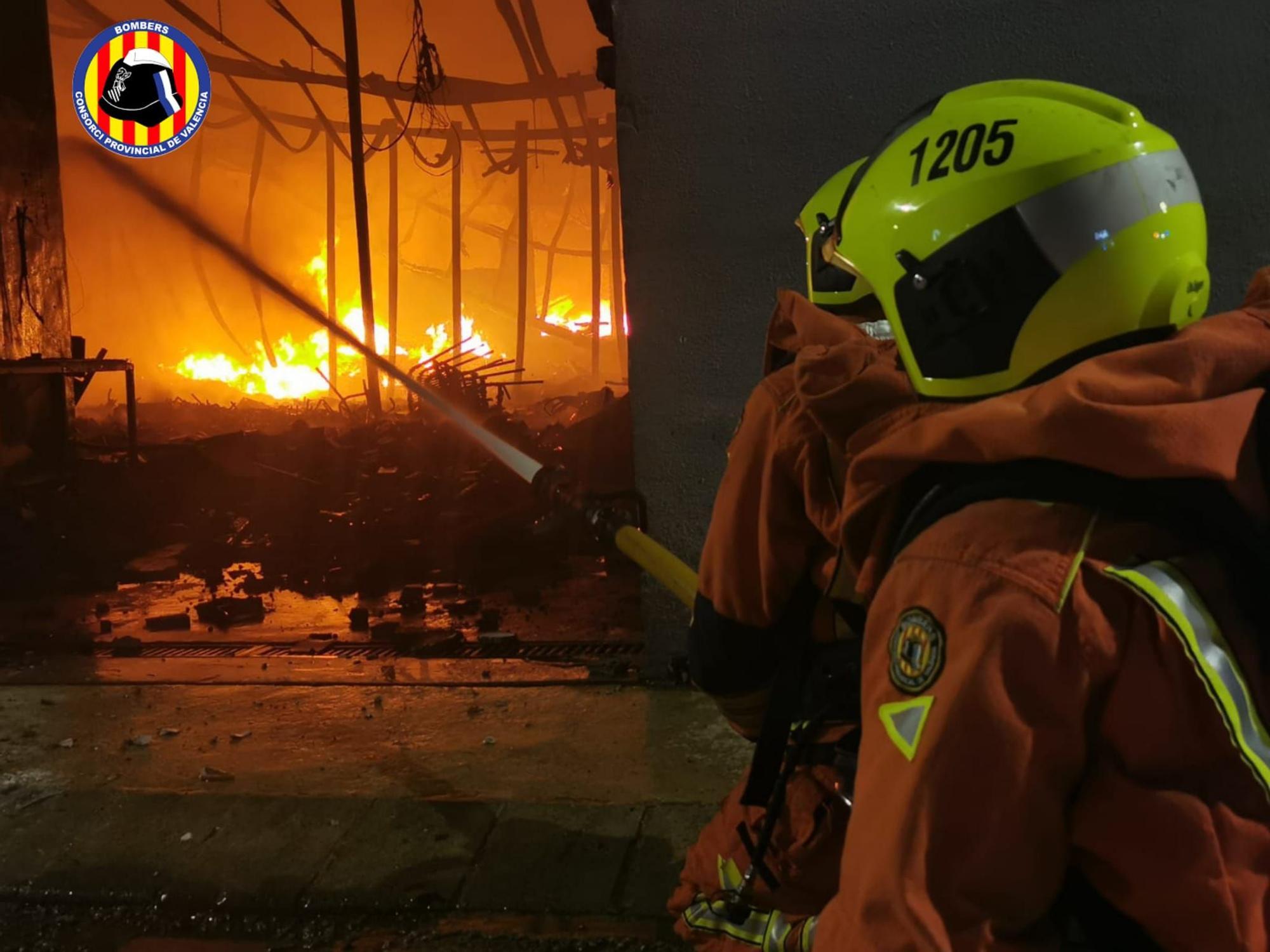 Así sofocan los bomberos las llamas de una nave industrial de Beniarjó