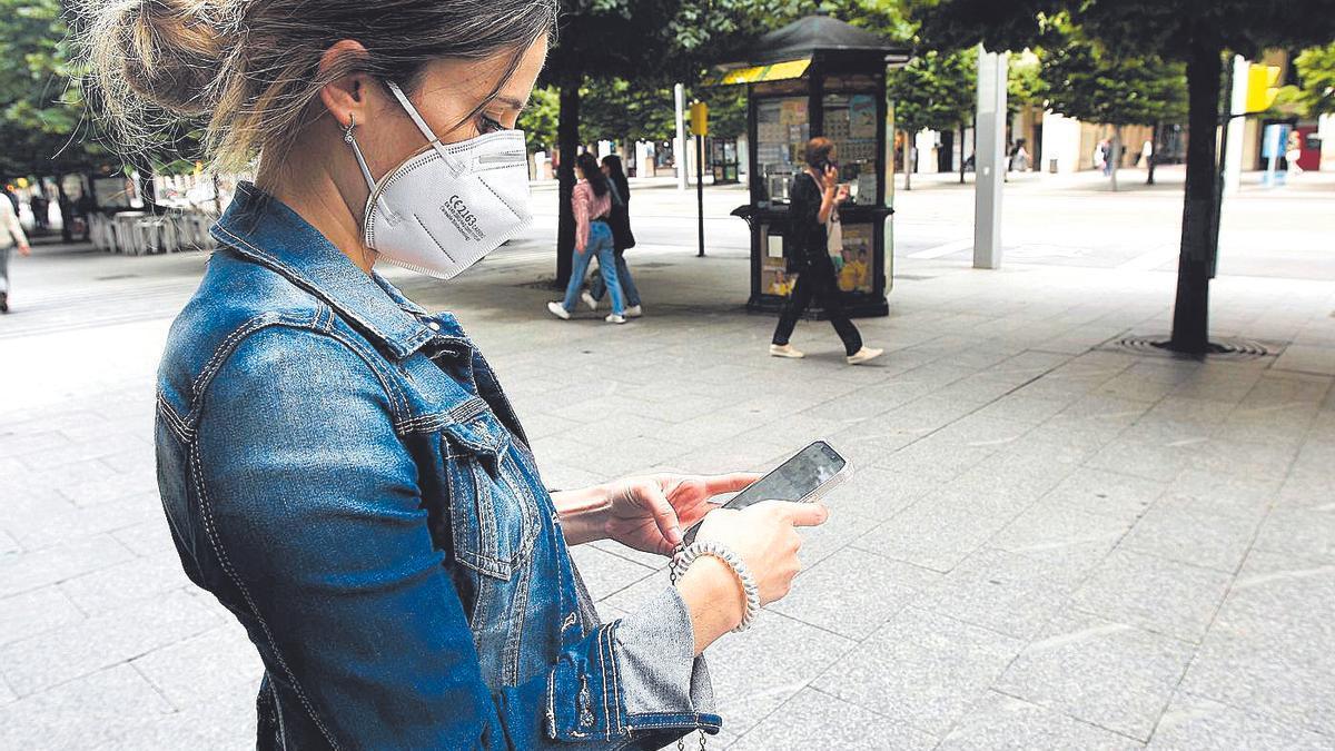 Una zaragozana mira atenta su móvil mientras camina por el paseo Independencia de Zaragoza
