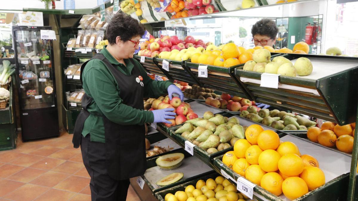 Una empleada ordena las estanterías de una frutería de Vigo.