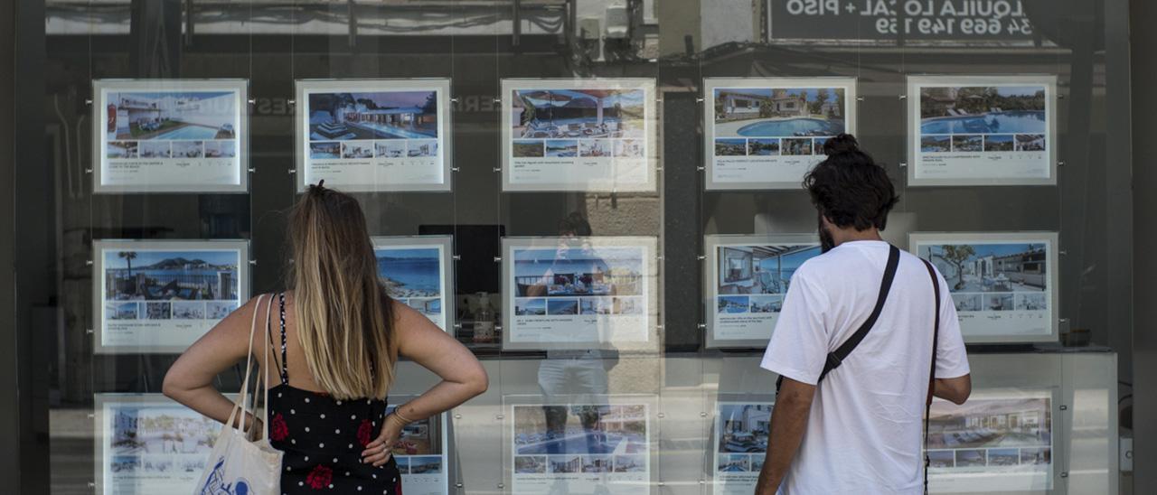 Dos personas observan los anuncios de una inmobiliaria