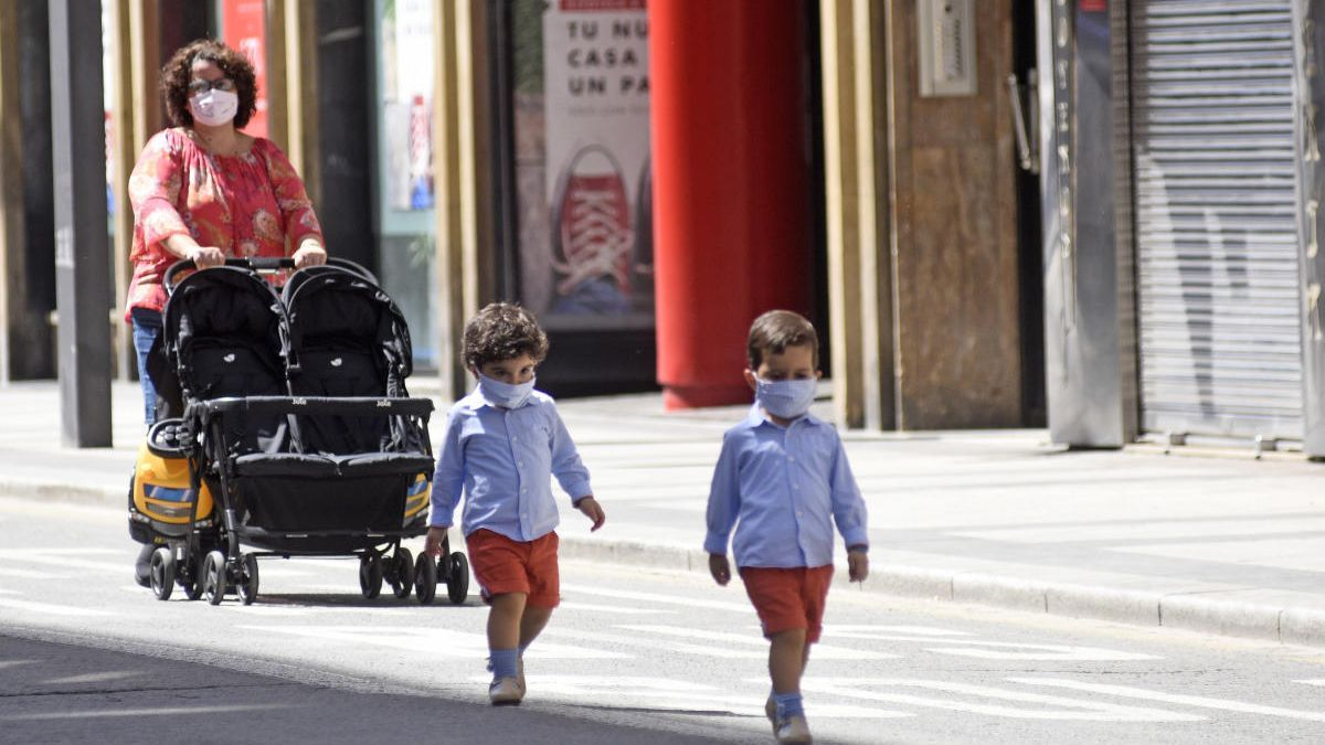 Unos niños pasean por la Gran Vía acompañados de su madre.