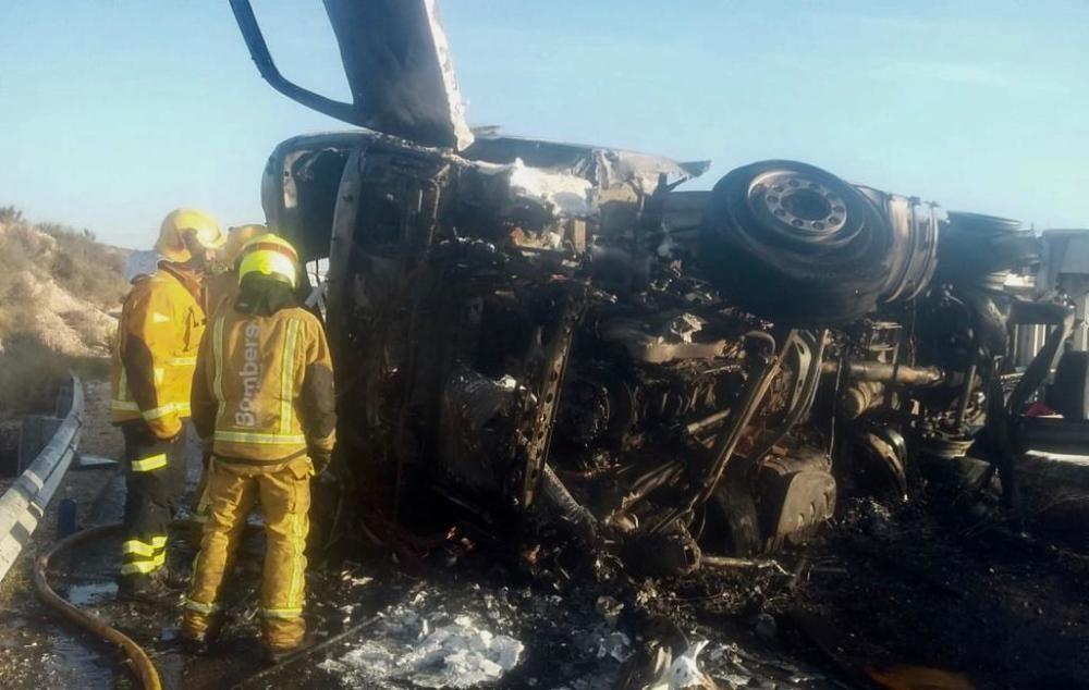 Los bomberos del Parque Comarcal de Elda refrigeran el tráiler que ha volcado y posteriormente se ha incendiado